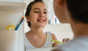 san mateo child checking teeth in mirror
