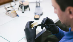 san mateo prosthodontist holding a mold of teeth
